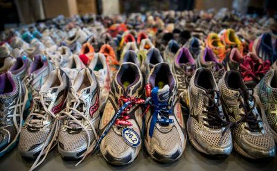 "BOSTON, MA - APRIL 14:  Runner's shoes are laid out in a display titled, ""Dear Boston: Messages from the Marathon Memorial"" in the Boston Public Library to commemorate the 2013 Boston Maraton bombings, on April 14, 2014 in Boston, Massachusetts. Last year, two pressure cooker bombs killed three and injured an estimated 264 others during the Boston marathon, on April 15, 2013.  (Photo by Andrew Burton/Getty Images) Photo: Getty Images / 2014 Getty Images"