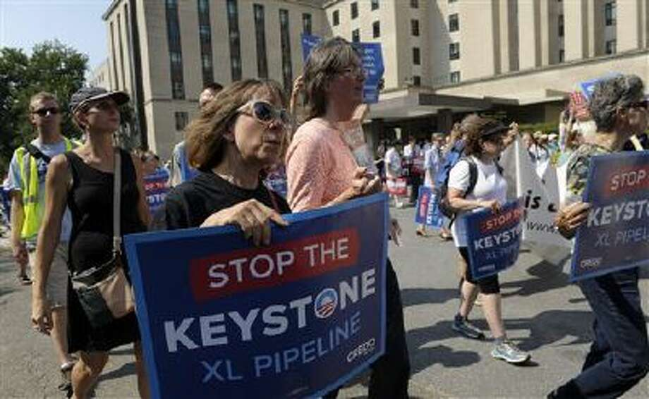 Protestors against the Keystone Pipeline rally outside the State Department in Washington, Monday, Aug. 12, 2013. (AP Photo/Susan Walsh) Photo: AP / AP