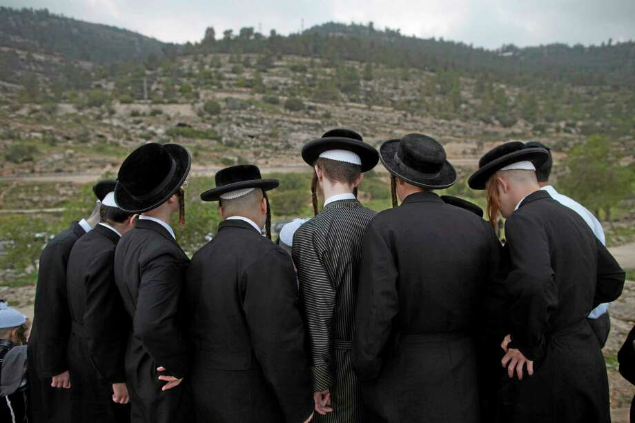 Ultra-Orthodox Jews collect water to make matza during the Maim Shelanoo ceremony at a mountain spring, near Jerusalem, Sunday, April 13, 2014. The water is used to prepare the traditional unleavened bread for the high holiday of Passover which begins Monday.(AP Photo/Dan Balilty) Photo: AP / AP