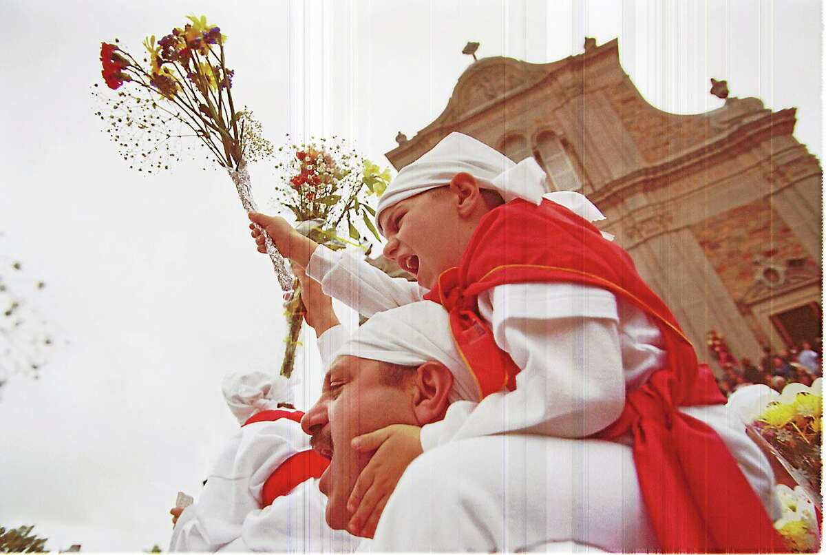 """Marcus Fazzino, 5, rides high on his father Nick's shoulders as they stream out of St. Sebastian's Church shouting """"prima diu e sammastianu"""" during the celebration of the Feast of St. Sebastian in this 2000 file photo."""
