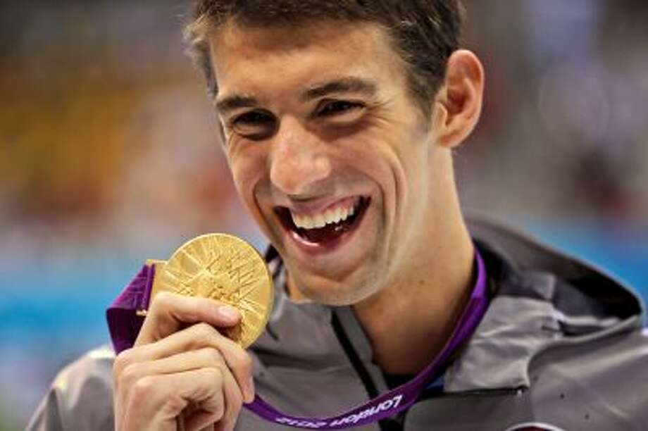 FILE - In this Aug. 3, 2012, file photo, United States' Michael Phelps displays his gold medal for the men's 100-meter butterfly swimming final at the Aquatics Centre in the Olympic Park during the 2012 Summer Olympics in London. Phelps is coming out of retirement, the first step toward possibly swimming at the 2016 Rio Olympics. Bob Bowman, the swimmer's longtime coach, told The Associated Press on Monday, April 14, 2014, that Phelps is entered in three events - the 50- and 100-meter freestyles and the 100 butterfly at his first meet since the 2012 London Games at a meet in Mesa, Ariz., on April 24-26. (AP Photo/Matt Slocum, File) Photo: AP / AP2012