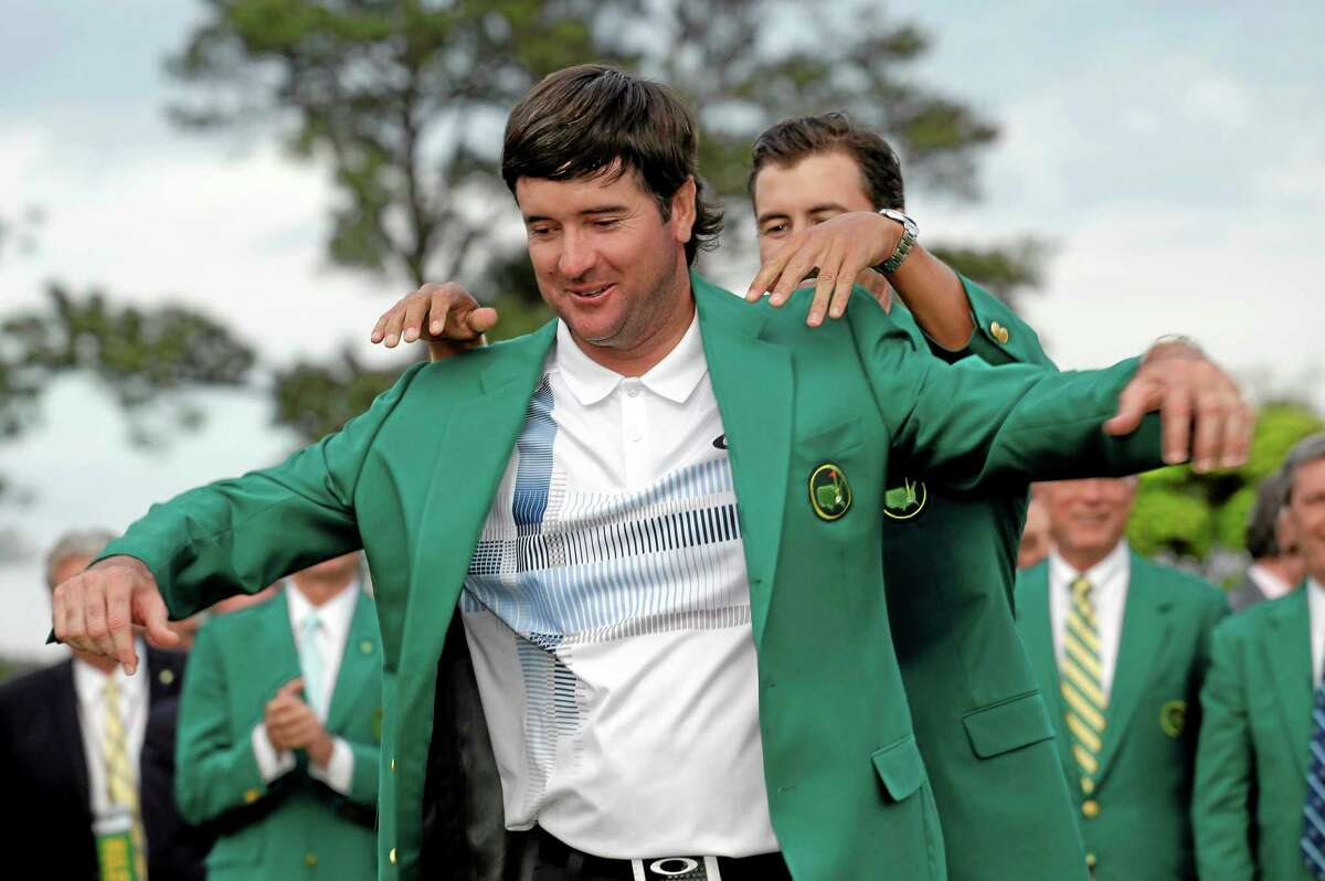 Defending Masters' champion Adam Scott helps Bubba Watson, left, with his green jacket after winning the Masters Sunday in Augusta, Ga. (AP Photo/David J. Phillip)
