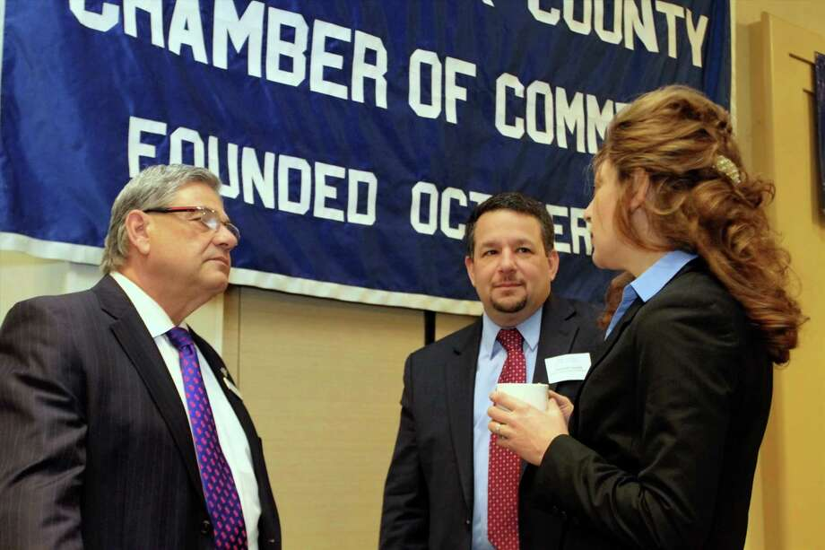 Liberty Bank Board of Directors Chairman Mark Gingras, left, and Chamber Vice Chairman Rich Carella, center, welcome UConn President Susan Herbst to the Business & Education meeting. Photo: De Kine Photo LLC  / (c)dekinephotoLLC2013