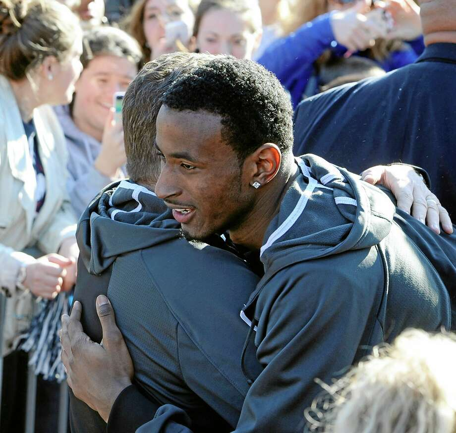 Connecticut men's basketball player DeAndre Daniels, right, hugs Connecticut women's head coach Geno Auriemma after Auriemma arrived on campus with his team for a rally celebrating their NCAA title on Wednesday, April 9, 2014, in Storrs, Conn. (AP Photo/Jessica Hill) Photo: AP / FR125654 AP