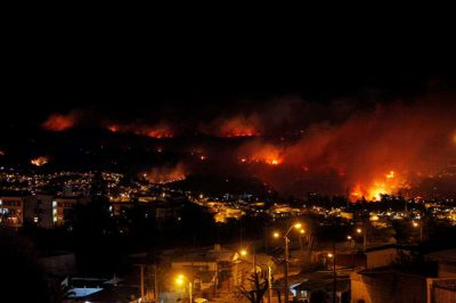 An out of control forest fire rages towards urban areas in the city of Valparaiso, Chile, Saturday, April 12, 2014. Authorities say the forest fire has destroyed at least 150 homes and is forcing evacuations. ( AP Photo/ Luis Hidalgo) Photo: AP / AP2014