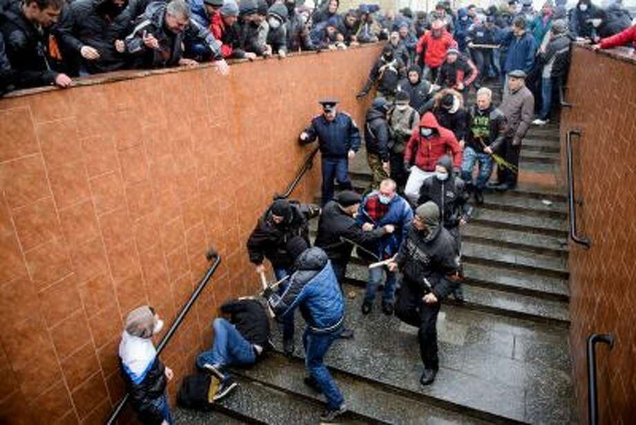 Pro-Russia supporters beat a pro-Western activist who lies on the stairs  during a pro Russian rally in Kharkiv, Ukraine, Sunday, April 13, 2014. Two rival rallies in Kharkiv turned violent after a group of pro-Russian protesters followed several pro-Ukrainian activists, beating them with baseball bats and sticks. (AP Photo/ Olga Ivashchenko) Photo: AP / AP