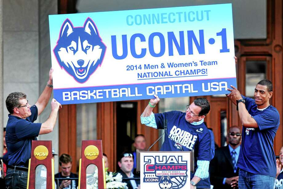 (Arnold Gold-New Haven Register)  UConn women's basketball coach Geno Auriemma, left, and UConn men's basketball coach Kevin Ollie, right, assist Gov. Dannel P. Malloy with a sign at a victory rally in front of the Capitol Building in Hartford. Photo: Journal Register Co.