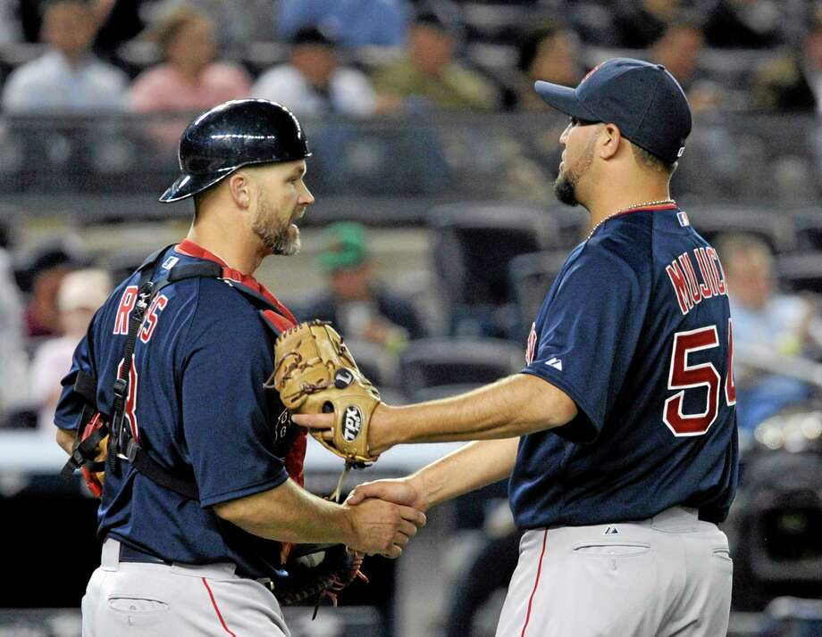 Red Sox pitcher Edward Mujica, right, celebrates Friday night's save against the Yankees with catcher David Ross. If Koji Uehara has a serious injury, Mujica immediately becomes the Boston closer. Photo: Bill Kostroun — The Associated Press  / FR51951 AP