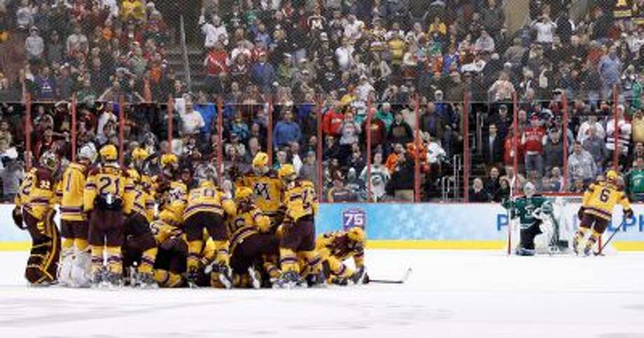 Minnesota gather around Justin Holl, who just scored the goal as Jake Parenteau (6) swings by North Dakota's Zane  Gothberg during the third period of an NCAA men's college hockey Frozen Four tournament game on Thursday, April 10, 2014, in Philadelphia. Minnesota won 2-1. (AP Photo/Chris Szagola) Photo: AP / FR170982 AP