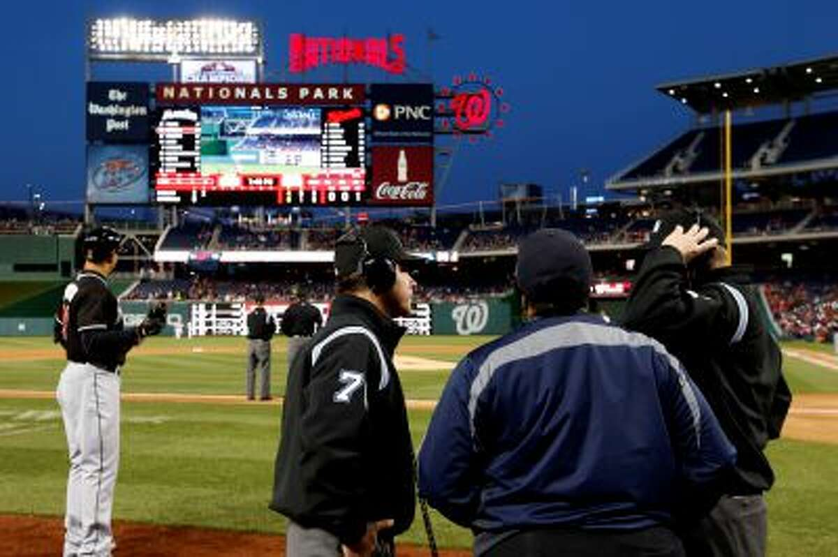 Umpires D.J. Reyburn, left, and Jeff Kellogg, right, listen to the replay umpires to rule Miami Marlins' Derek Dietrich hit a two-run homer during the second inning of a baseball game against the Washington Nationals at Nationals Park Wednesday, April 9, 2014, in Washington. (AP Photo/Alex Brandon)