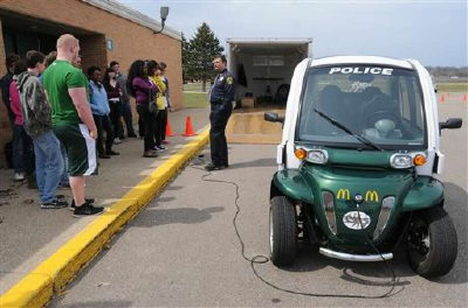 Berrien Springs Oronoko Township Deputy Police Chief Rick Smiedendorf talks with Berrien Springs High School juniors as they prepare to drive a GEM (Global Electric Motors) car through an obstacle course Thursday, April 10, 2014, at Berrien Springs High School, in Berrien Springs, Mich. Students had the opportunity to drive and ride in the vehicle while wearing goggles simulating various levels of alcohol use. The car is part of the Berrien Springs Oronoko Township Police Department's IDDEA (Intoxicated, Distracted, Driver Education Awareness) program designed to teach students about the dangers of drunk and distracted driving.(AP Photo/The Herald-Palladium, Don Campbell) Photo: AP / The Herald-Palladium