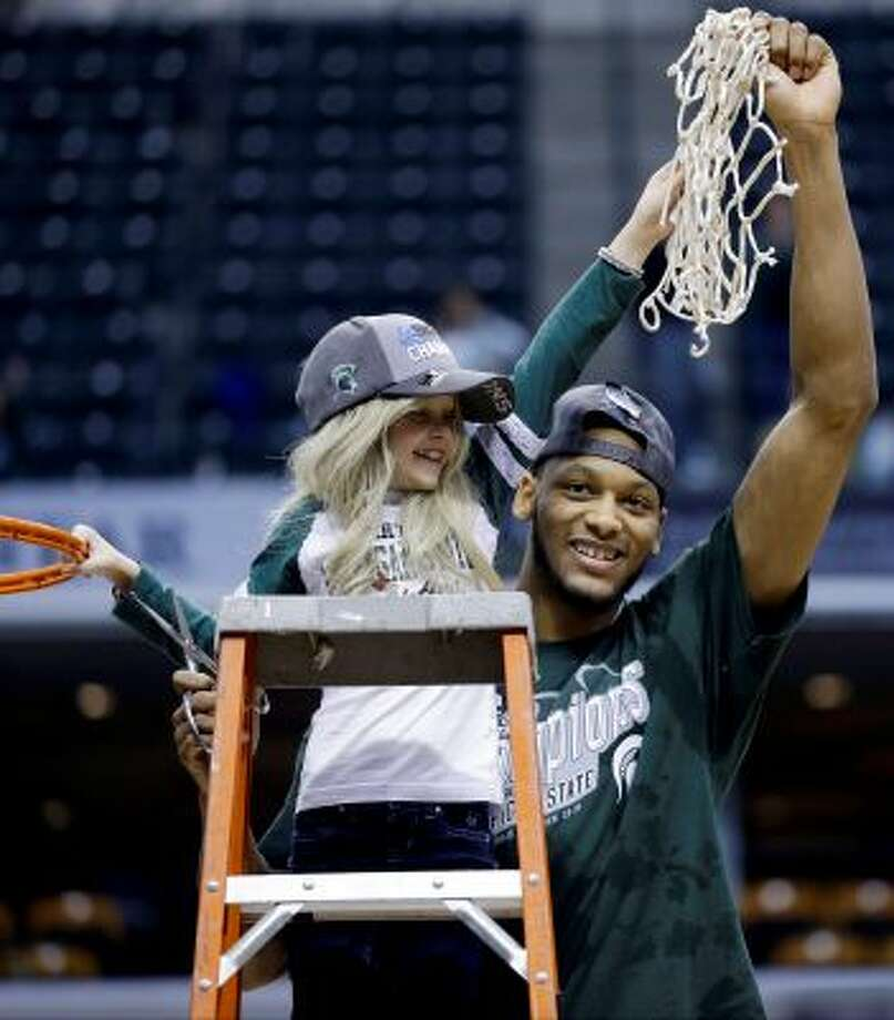 "FILE - In this March 16, 2014 file photo, Michigan State forward Adreian Payne, right, hoists the net with Lacey Holsworth, who is battling cancer, after Michigan State defeated Michigan 69-55 in an NCAA college basketball game in the championship of the Big Ten Conference tournament in Indianapolis. The father of  8-year-old Lacey Holsworth, who befriended Michigan State basketball star Adreian Payne says his daughter has died. Matt Holsworth says Lacey Holsworth died at their St. Johns, Mich., home late Tuesday, April 8, 2014 ""with her mommy and daddy holding her in their arms."" (AP Photo/Michael Conroy, File) Photo: AP / THE ASSOCIATED PRESS2014"