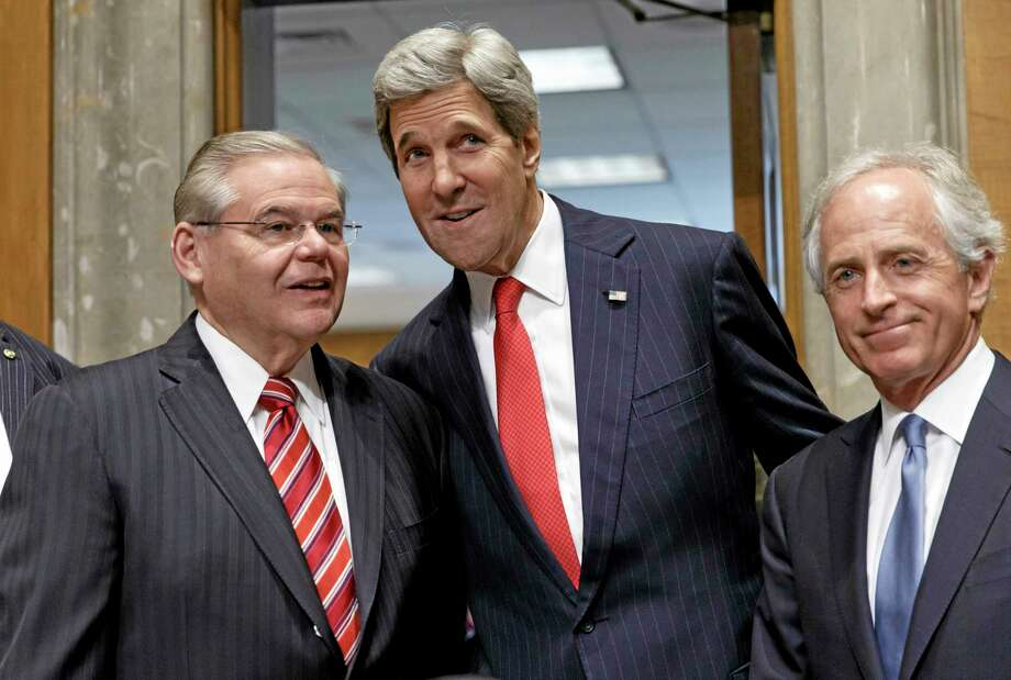 Secretary of State John Kerry, flanked by Senate Foreign Relations Chairman Sen. Robert Menendez, D-N.J., left, and Sen. Bob Corker, R-Tenn., the ranking committee member, arrives on Capitol Hill in Washington, Tuesday, April 8, 2014, to appear before the committee he used to lead to discuss his budget and the status of diplomatic hot spots. Lawmakers' questions focused on Russia, Ukraine, Iran and Syria. (AP Photo/J. Scott Applewhite) Photo: AP / AP