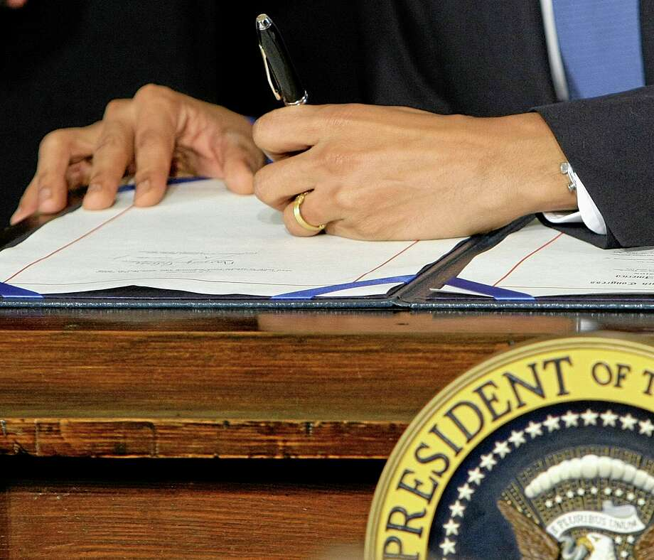 FILE - In this March 23, 2010, file photo President Barack Obama signs the health care bill in the East Room of the White House in Washington. As a hectic sign-up season winds down, President Barack Obama's health care law has managed to change the country. Americans are unlikely to go back to a time when people with medical problems could be denied coverage. But Obamaís overhaul needs reworking of its own to go down in history as a legacy achievement like Medicare and Social Security.(AP Photo/J. Scott Applewhite, File) Photo: AP / AP