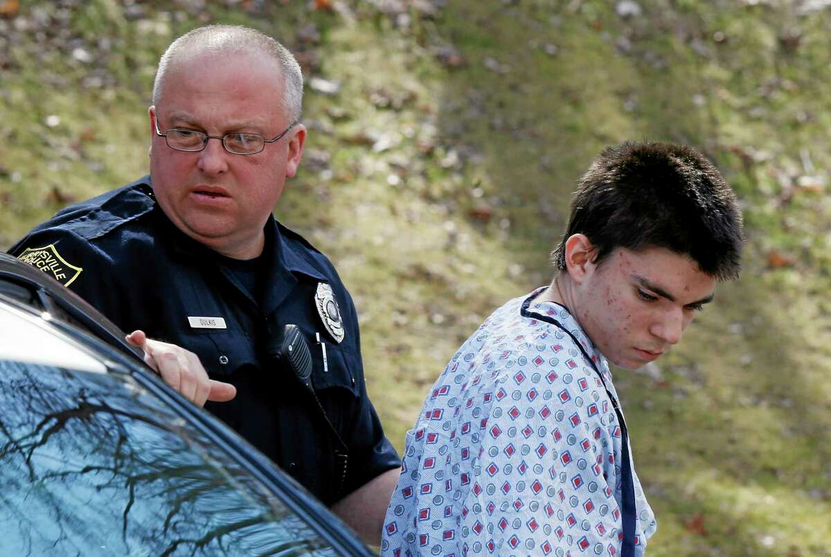 Alex Hribal, the suspect in the multiple stabbings at the Franklin Regional High School in Murrysville, Pa., is escorted by police to a district magistrate to be arraigned on Wednesday, April 9, 2014, in Export, Pa. Authorities say Hribal has been charged with allegedly stabbing and slashing 19 students and a police officer in the crowded halls of his suburban Pittsburgh high school Wednesday. (AP Photo/Keith Srakocic)