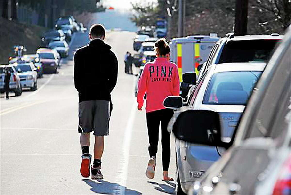 Students walk down the street away from the campus of the Franklin Regional School District, where several people were stabbed at Franklin Regional High School, on Wednesday, April 9, 2014, in Murrysville, Pa., near Pittsburgh. The suspect, a male student, was taken into custody and being questioned.