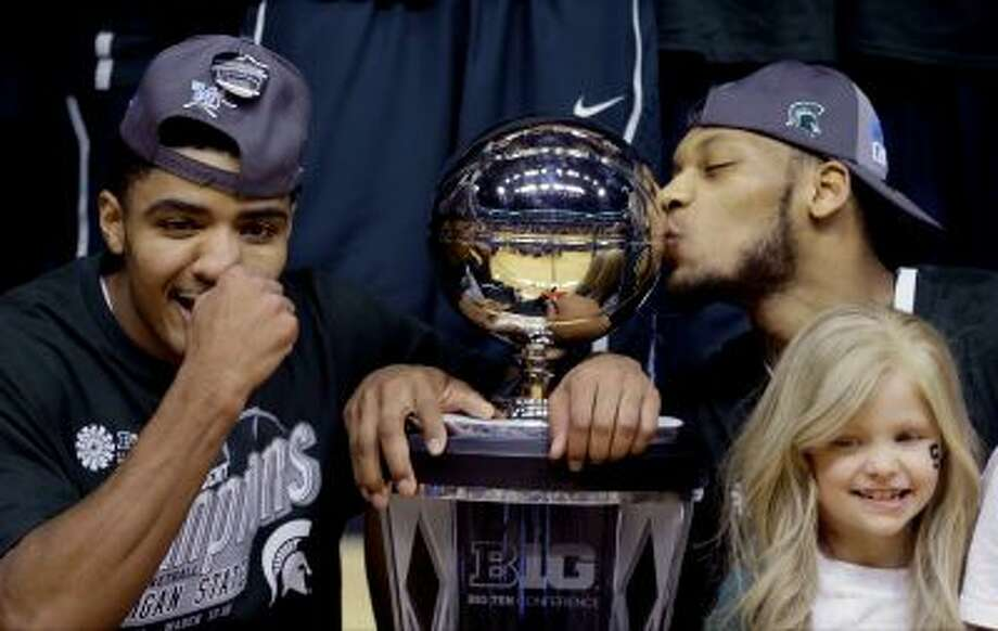 """FILE - In this March 16, 2014 file photo, Michigan State's Gary Harris, left, poses with the championship trophy as Adreian Payne kisses it after they  defeated Michigan 69-55 in an NCAA college basketball game in the championship of the Big Ten Conference tournament in Indianapolis. Lacey Holsworth, who is batling cancer,  smiles at right foreground. The father of  8-year-old Lacey Holsworth, who befriended Michigan State basketball star Adreian Payne says his daughter has died. Matt Holsworth says Lacey Holsworth died at their St. Johns, Mich., home late Tuesday, April 8, 2014, """"with her mommy and daddy holding her in their arms.""""(AP Photo/Michael Conroy) Photo: AP / AP"""