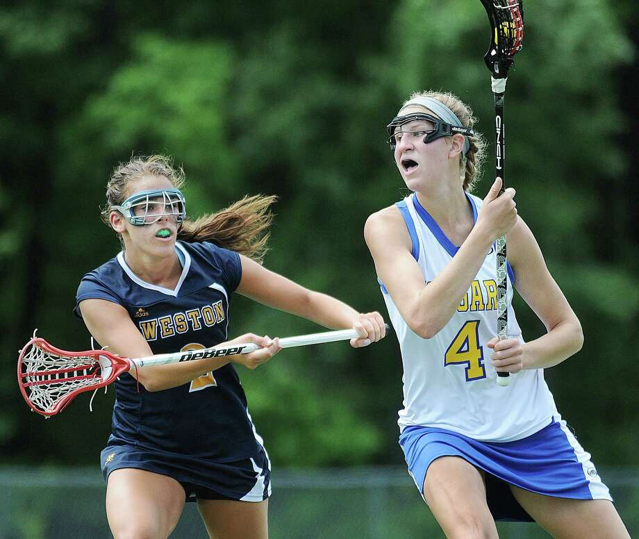 Haddam-Killingworth senior Kiley Anderson moves the ball toward the Weston goal as Morgan Moubayed defends in the CIAC Lacrosse Class S State Championship game last season. Photo: Catherine Avalone — The Middletown Press  / TheMiddletownPress