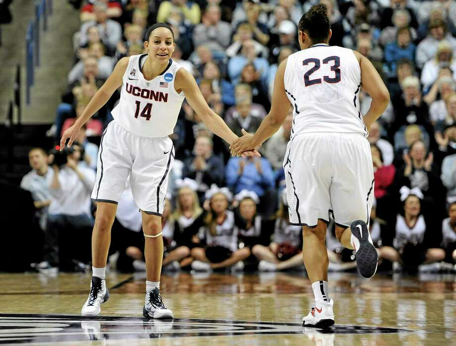 Connecticut's Bria Hartley and Kaleena Mosqueda-Lewis slap hands during the second half of a second-round game of the NCAA women's college basketball tournament, Tuesday, March 25, 2014, in Storrs, Conn.  Connecticut won 91-52. (AP Photo/Jessica Hill) Photo: AP / FR125654 AP