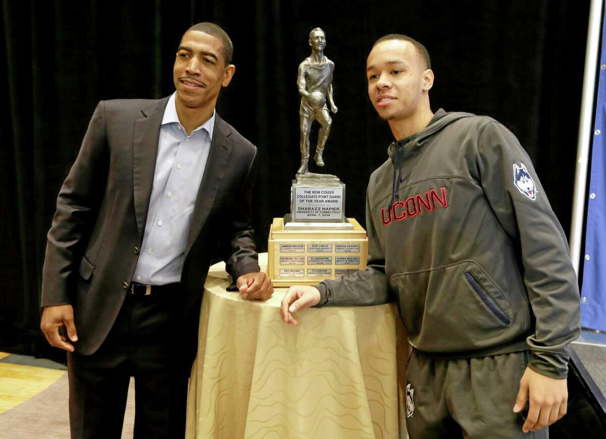Connecticut head coach Kevin Ollie, left, and guard Shabazz Napier pose with the trophy before Napier was awarded the Bob Cousy Collegiate Point Guard of the Year Award, Monday, April 7, 2014, in Dallas. (AP Photo/Charlie Neibergall)