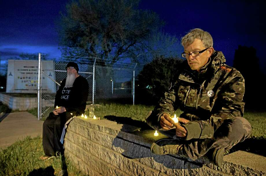 """Army veterans David Bass, left, Michael Clift participate in a candlelight vigil for the victims of Wednesday's shooting at Fort Hood, at the East Gate of the Texas military base, on Friday, April 4, 2014. The Fort Hood soldier who gunned down three other military men before killing himself had an argument with colleagues in his unit before opening fire, and investigators believe his mental condition was not the """"direct precipitating factor"""" in the shooting, authorities said Friday. (AP Photo/Austin American-Statesman, Jay Janner) Photo: AP / Austin American-Statesman"""