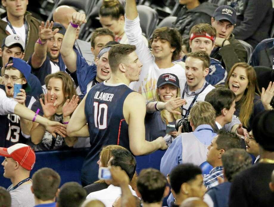 Connecticut fans celebrate with forward Tyler Olander after their team beat Florida 63-53 at their NCAA Final Four tournament college basketball semifinal game Saturday, April 5, 2014, in Arlington, Texas. (AP Photo/Tony Gutierrez) Photo: AP / AP