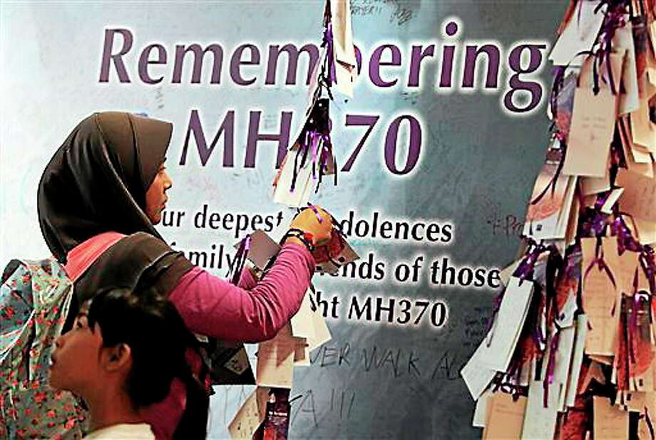 A woman ties a message card for passengers aboard the missing Malaysia Airlines flight MH370, at a shopping mall in Kuala Lumpur, Malaysia, Saturday, April 5, 2014. Search teams racing against time to find the flight recorders from the missing Malaysia Airlines jet crisscrossed another patch of the Indian Ocean on Saturday, four weeks to the day after the airliner vanished. (AP Photo/Lai Seng Sin) Photo: AP / AP