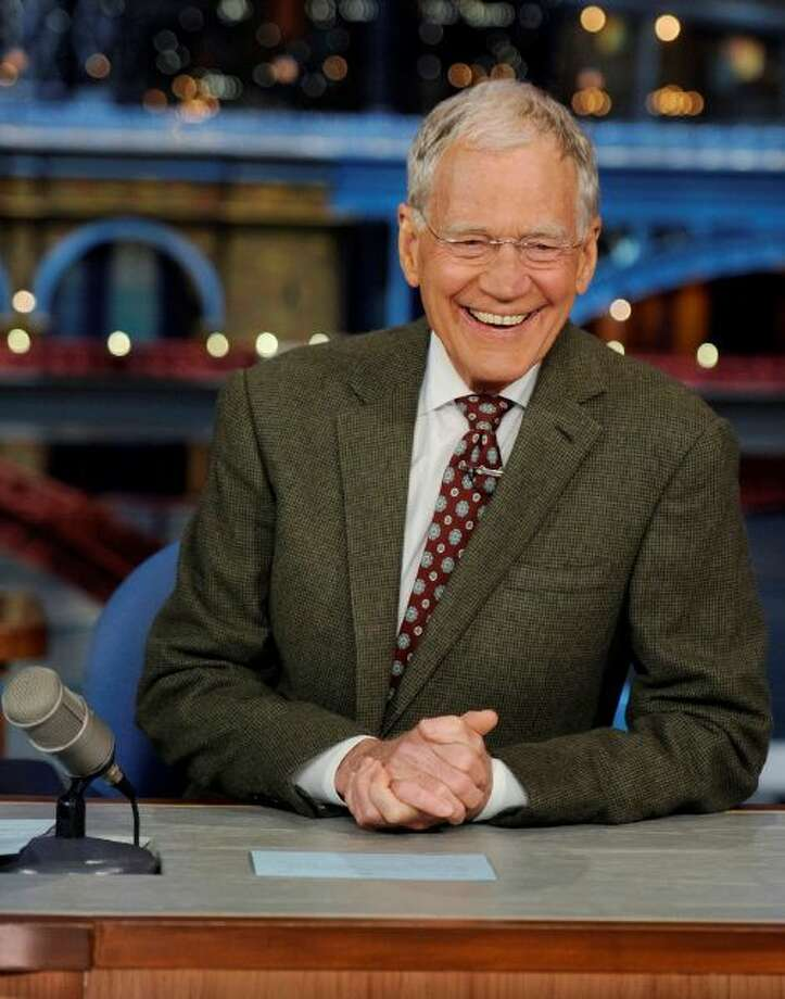 "In this photo provided by CBS, David Letterman, host of the ""Late Show with David Letterman,"" smiles while seated at his desk in New York on Thursday, April 3, 2014. Letterman announced his retirement during Thursday's taping. Although no specific date was announced he told the audience that he will leave his desk sometime in 2015. (AP Photo/CBS, Jeffrey R. Staab) MANDATORY CREDIT, NO SALES, NO ARCHIVE, FOR NORTH AMERICAN USE ONLY Photo: AP / CBS"