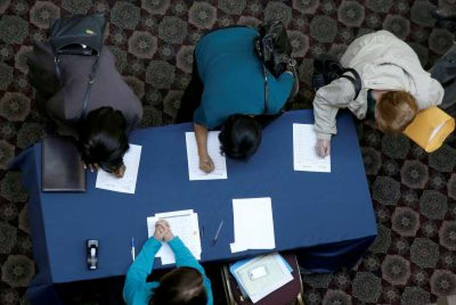 FILE - In this Jan. 22, 2014, file photo, job seekers sign in before meeting prospective employers during a career fair at a hotel in Dallas. The Labor Department releases weekly jobless claims, on Thursday, April 3, 2014. (AP Photo/LM Otero) Photo: AP / AP