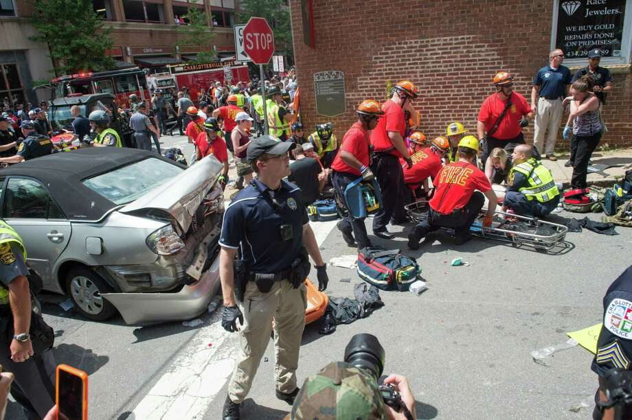 A woman is received first-aid after a car accident ran into a crowd of protesters in Charlottesville, VA on August 12, 2017.  A picturesque Virginia city braced Saturday for a flood of white nationalist demonstrators as well as counter-protesters, declaring a local emergency as law enforcement attempted to quell early violent clashes.  / AFP PHOTO / PAUL J. RICHARDSPAUL J. RICHARDS/AFP/Getty Images Photo: PAUL J. RICHARDS / AFP/Getty Images / AFP or licensors