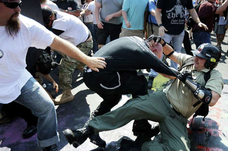 """CHARLOTTESVILLE, VA - AUGUST 12:  White nationalists, neo-Nazis and members of the """"alt-right"""" clash with counter-protesters as they enter Lee Park during the """"Unite the Right"""" rally August 12, 2017 in Charlottesville, Virginia. After clashes with anti-fascist protesters and police the rally was declared an unlawful gathering and people were forced out of Lee Park, where a statue of Confederate General Robert E. Lee is slated to be removed.  (Photo by Chip Somodevilla/Getty Images) Photo: Chip Somodevilla / Getty Images / 2017 Getty Images"""