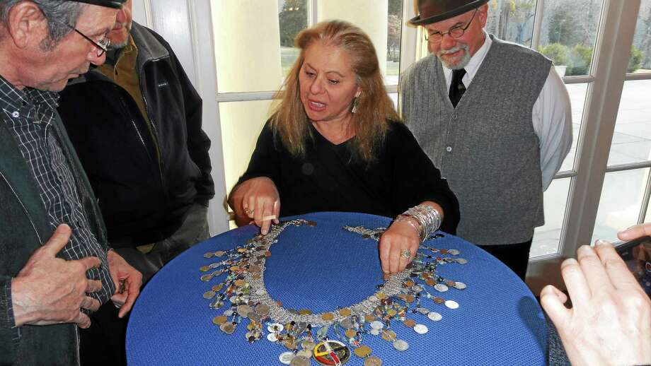 During Arts Advocacy Awards at the Wadsworth Mansion in Middletown, Artists For World Peace founder, jewelry designer Wendy Black Nasta, explains the International Peace Belt. Photo: Cassandra Day — The Middletown Press