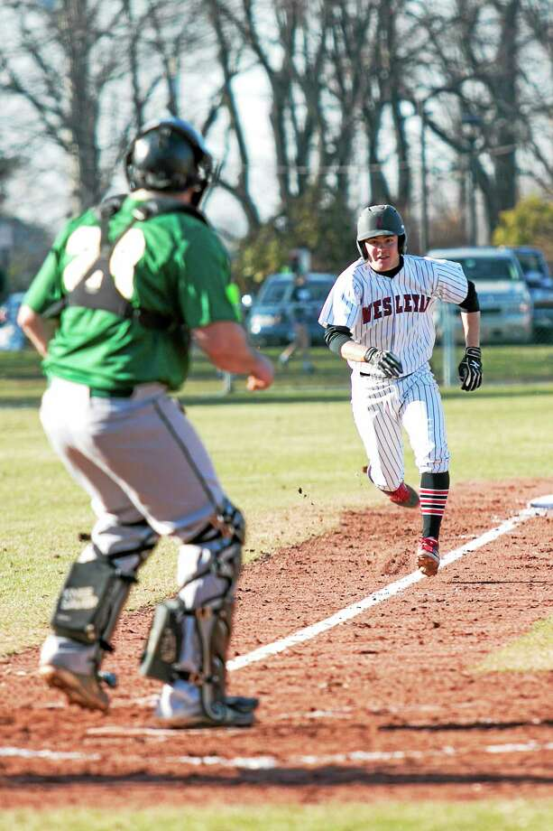 Wesleyan freshman Ellis Schaefer tries to score in the fourth inning of the Cardinals 15-2 victory against Elms College. Photo: Sandy Aldieri — Special To The Press