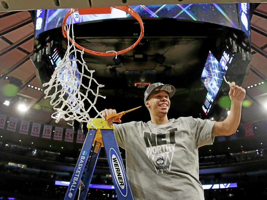 Connecticut's Shabazz Napier smiles after cutting the net after a regional final against Michigan State in the NCAA college basketball tournament Sunday, March 30, 2014, in New York. Connecticut won the game 60-54. (AP Photo/Seth Wenig) Photo: AP / AP