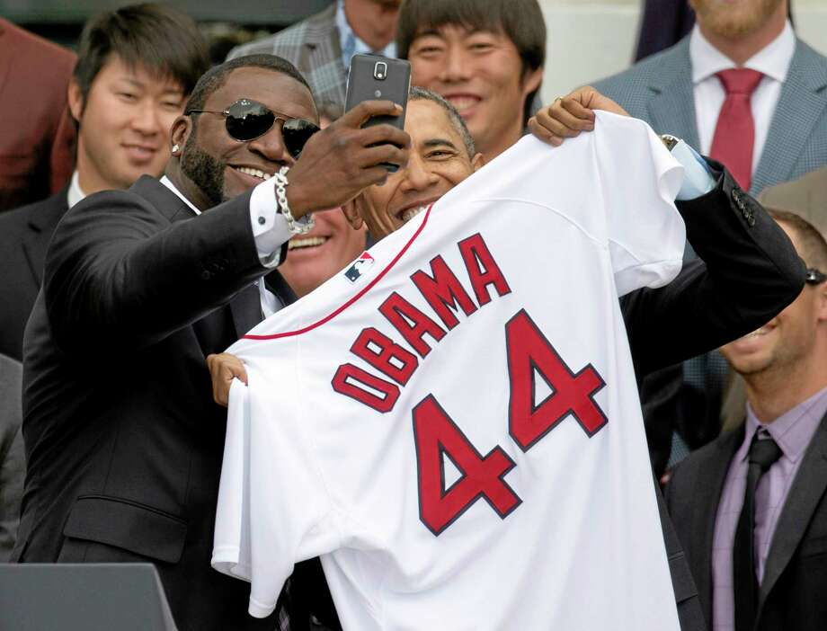 Boston Red Sox designated hitter David Ortiz takes a selfie with President Barack Obama, holding a jersey presented to the president during a ceremony on the South Lawn of the White House in Washington on Tuesday as the president honored the 2013 World Series champions. In the background are pitchers Junichi Tazawa, left, and Koji Uehara. Photo: Carolyn Kaster — The Associated Press  / AP