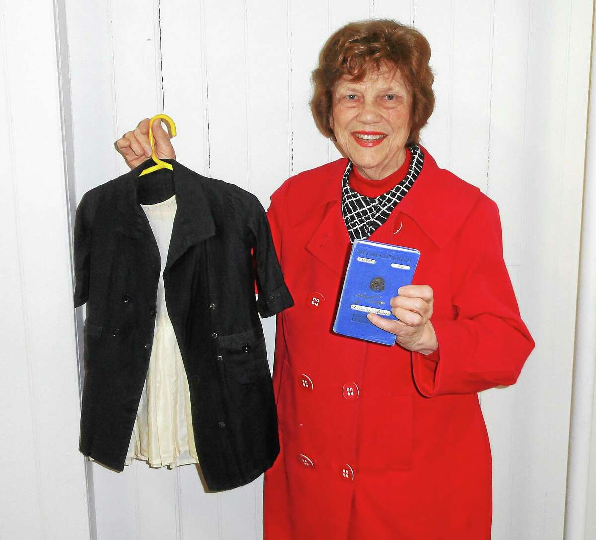 Barbara Arafeh of the Greater Middletown Concert Association holds the outfit that Angela Mancini Chiarappa of Middletown wore when she came through Ellis Island from Turi, Italy, at age 4.