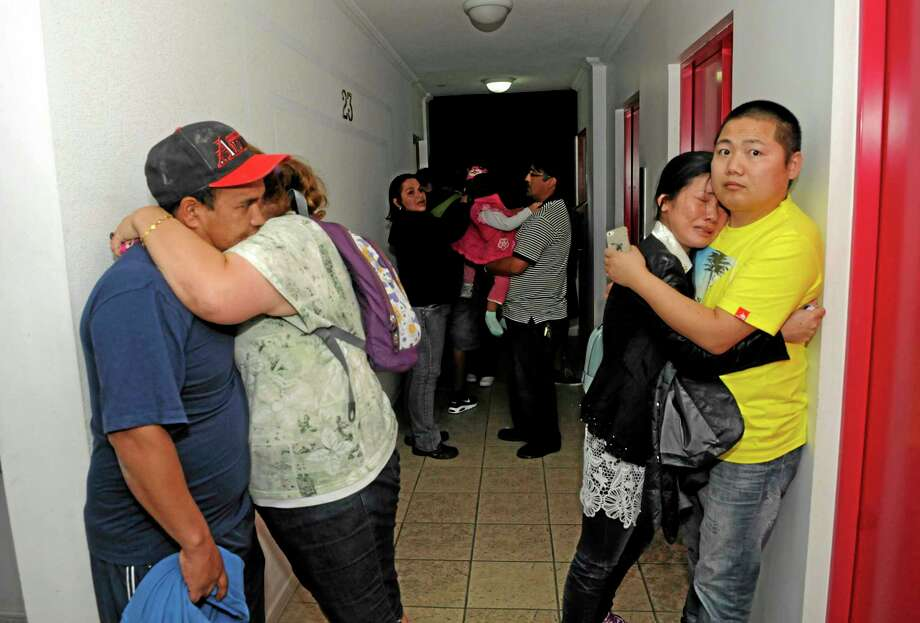 People embrace on the upper floor of an apartment building located a few blocks from the coast where they gathered to avoid a possible tsunami after an earthquake in Iquique, Chile, Tuesday, April 1, 2014. A powerful magnitude-8.2 earthquake struck off Chile's northern coast Tuesday night. There were no immediate reports of injuries or major damage, but buildings shook in nearby Peru and in Bolivia's high altitude capital of La Paz. (AP Photo/Cristian Viveros) NO PUBLICAR EN CHILE Photo: AP / AP