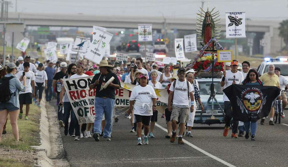 """Hundreds take part in a march and rally in opposition to the Trump administration's pursuit of a border wall in the Rio Grande Valley on Saturday, Aug. 12, 2017. They gathered at Our Lady of Guadalupe Catholic Church in Mission, Texas for a march and rally which ended at La Lomita Mission which resides behind a levy along the Rio Grande River. Organizers such as Scott Nicol from Lower Rio Grande Valley Sierra Club fears that a proposed levy wall will undermine the historic site. """"The ultimate goal (of the rally) is to show the rest of the nation that border residents reject border walls,"""" Nicol said. The four-mile long march concluded as people made their way along a section of a levy leading to La Lomita Mission which was established in 1865. Oblate priests and missionaries first utilized the site as they visited Catholic churches around the Rio Grande Valley performing marriages and blessing the dead. People around the state and nation attended the march and rally according to Nicol. Among the participants was San Antonian Annette Ivy who carried a sign opposed to a wall being built at La Lomita. Ivy's brother was once a resident at La Lomita Farms - a facility that once exited on the site for developmentally disabled adults. """"It was a great facility,"""" Ivy said, """"The old chapel is beautiful and it is a shame to have it cut off."""" (Kin Man Hui/San Antonio Express-News) Photo: Kin Man Hui, Staff / San Antonio Express-News / ©2017 San Antonio Express-News"""
