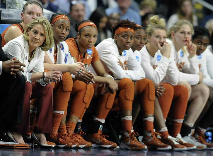 Texas coach Karen Aston (left) and her team watch the end of a loss to Connecticut in the regional final of the NCAA Tournament on March 28, 2016, in Bridgeport, Conn.