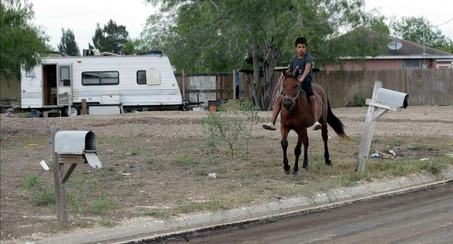 A boy rides a horse through Indian Hills East colonia near Alamo. Texas has more than 2,300 colonias. Photo: Eric Gay, STF / Copyright 2017 The Associated Press. All rights reserved.