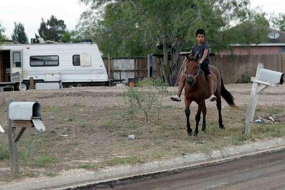 A boy rides a horse through Indian Hills East colonia near Alamo. Texas has more than 2,300 colonias.