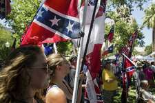 """Rachel Hall holds a flag and listens as Lamar """"Smoke"""" Russell raps during a rally held by Texas Freedom Force to protest the removal of the confederate monument in Travis Park in San Antonio, Texas on August 12, 2017.  Texas Freedom Force, a group dedicated to protecting Texas history, hosted a rally to protest the removal of the confederate monument. At the same time, SATX4, a community organization similar to Black Lives Matter, held a counter-protest."""