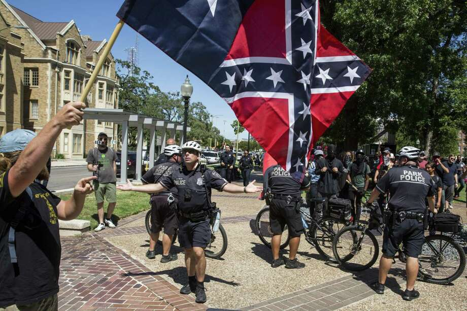 Police tell a man from the Texas Freedom Force rally to step away from a rally held by SATX4 to support the removal of the Confederate monument.Click through the slideshow to view some places in Texas where remnants of the Confederacy are alive and well. Photo: Carolyn Van Houten /San Antonio Express-News / 2017 San Antonio Express-News
