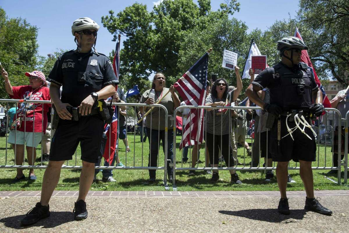 Police stand watch during a rally held by Texas Freedom Force to protest the removal of the confederate monument in Travis Park in San Antonio, Texas on August 12, 2017. Texas Freedom Force, a group dedicated to protecting Texas history, hosted a rally to protest the removal of the confederate monument. At the same time, SATX4, a community organization similar to Black Lives Matter, held a counter-protest.