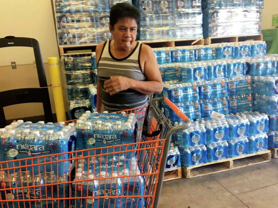"A resident buys bottles of water at Home Depot in Guam Saturday, Aug. 12, 2017. The small U.S. territory of Guam has become a focal point after North Korea's army threatened to use ballistic missiles to create an ""enveloping fire"" around the island. The exclamation came after President Donald Trump warned Pyongyang of ""fire and fury like the world has never seen."" (AP Photo/Tassanee Vejpongsa) ORG XMIT: TKTT701 Photo: Tassanee Vejpongsa / AP"