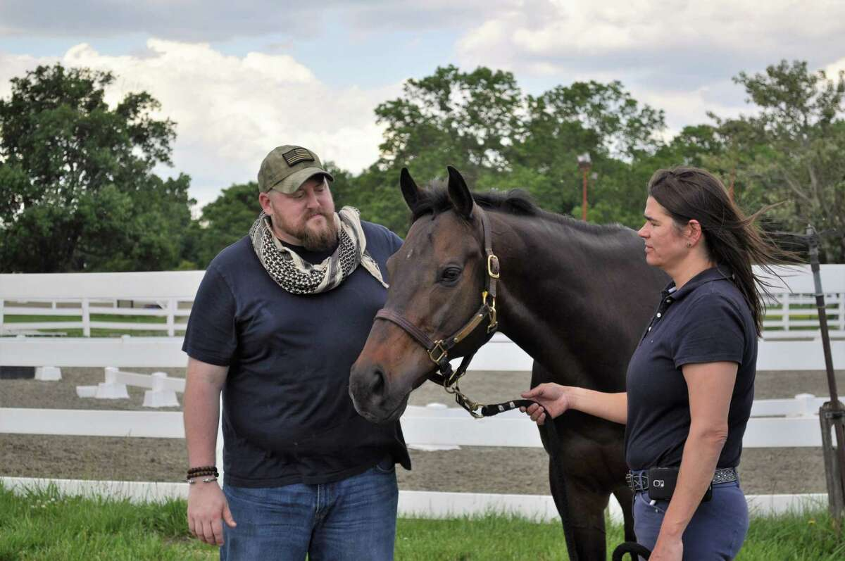 Retired Marine Sgt. Matt Ryba with Crafty Star, a 9-year-old retired race horse, and a staff member at the Bergen Equestrian Center in New Jersey, where the Man O' War program runs. (Provided)