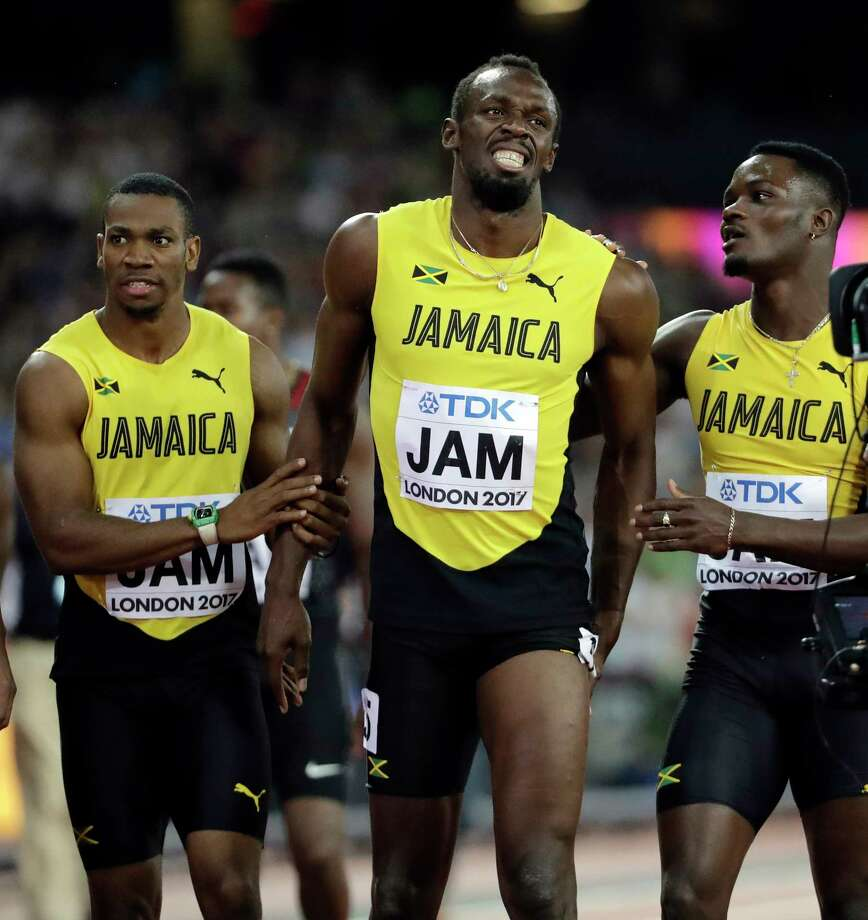 Jamaica's Usain Bolt, center, is assisted after he pulled up injured in the final of the Men's 4x100m relay during the World Athletics Championships in London Saturday, Aug. 12, 2017. (AP Photo/David J. Phillip) ORG XMIT: WTF611 Photo: David J. Phillip / Copyright 2017 The Associated Press. All rights reserved.