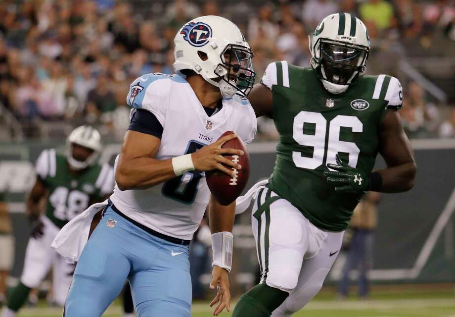 Tennessee Titans quarterback Marcus Mariota (8) runs the ball under pressure from New York Jets defensive end Muhammad Wilkerson (96) during the first quarter of an NFL football game, Saturday, Aug. 12, 2017, in East Rutherford, N.J. (AP Photo/Julio Cortez) ORG XMIT: ERU109 Photo: Julio Cortez / Copyright 2017 The Associated Press. All rights reserved.