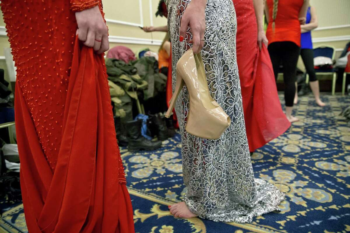 A Russia-backed female rebel fighter holds shoes before a beauty contest involving women from the main separatist battalions in Donetsk, Ukraine, Saturday, March 7, 2015. Self-proclaimed authorities in the rebel-held Donetsk held a beauty pageant for female rebel fighters on the eve of March 8, a women's day widely celebrated throughout the former Soviet Union.(AP Photo/Vadim Ghirda)