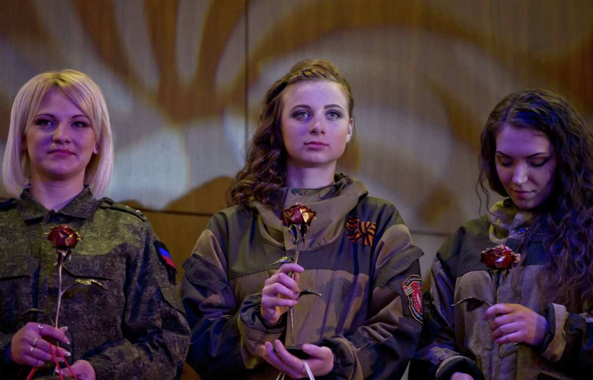 Russia-backed female rebel fighters stand on stage after taking part in a beauty contest involving women from the main separatist battalions in Donetsk, Ukraine, Saturday, March 7, 2015. Self-proclaimed authorities in the rebel-held Donetsk held a beauty pageant for female rebel fighters on the eve of March 8, a women's day widely celebrated throughout the former Soviet Union.(AP Photo/Vadim Ghirda)